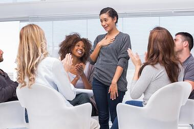 Smiling patient standing and telling her problems during therapy group session