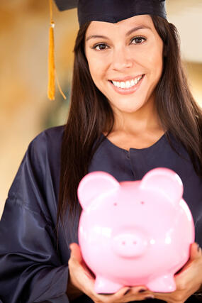 Graduate woman holding a piggybank with her education savings | Hocking College Debuts All-Inclusive Pricing Model