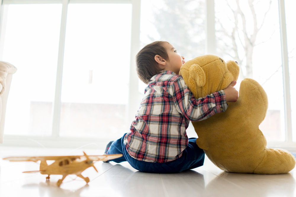 Little baby kid sitting in living room with toy bear | Tips for Finding a Temporary Holiday Job