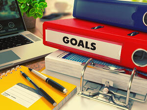Red Office Folder with Inscription Goals on Office Desktop with Office Supplies and Modern Laptop. Business Concept on Blurred Background. Toned Image.