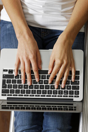 Womans hands typing on a modern laptop computer