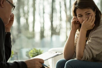 Young depressed woman taking advice from her psychologist | September is National Suicide Prevention Awareness Month