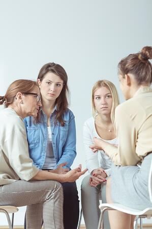 Young woman confiding problem to her support group